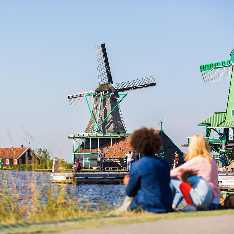 Two people sitting near the water looking at the Dutch windmills of the Zaanse Schans.