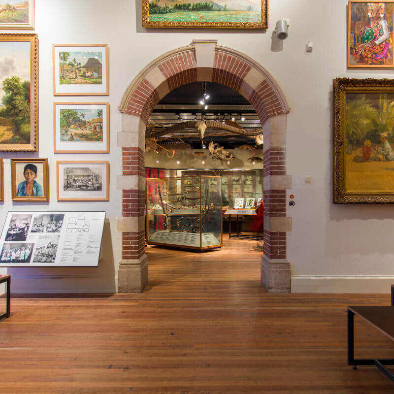 An alcove in the Tropenmuseum Amsterdam surrounded by a variety of paintings.