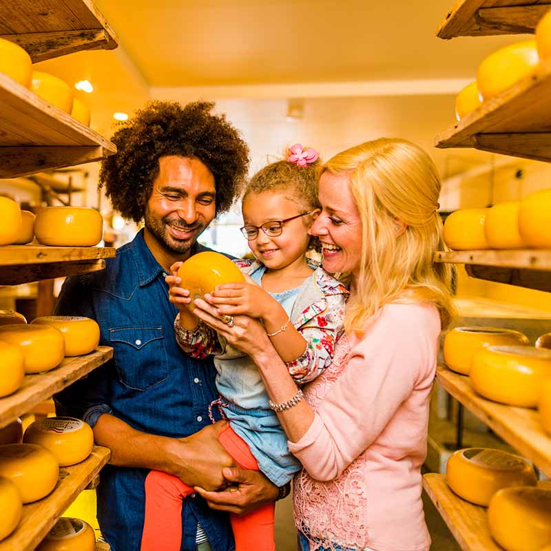 Couple with kid in the Cheesefactory in Volendam looking at cheeses.