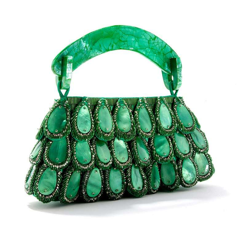 A small green bag with green scales hanging on it at the Museum of bags and purses in Amsterdam.