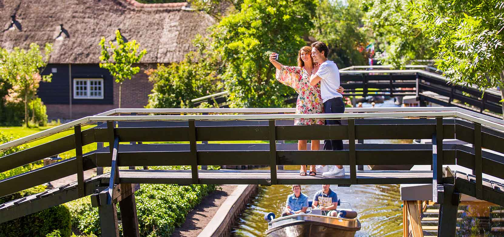 Couple taking a selfie on a bridge in Giethoorn with house and canal with a boat in the back.