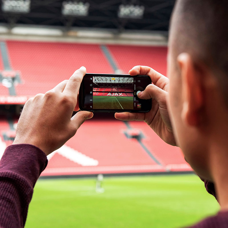 Guy taking a picture insight the Johan Cruijff Arena in Amsterdam.