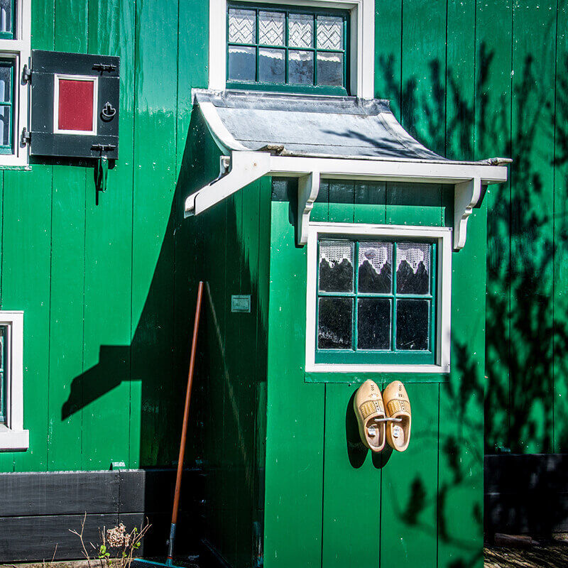 Typical authentic green Dutch house with clogs on the door.