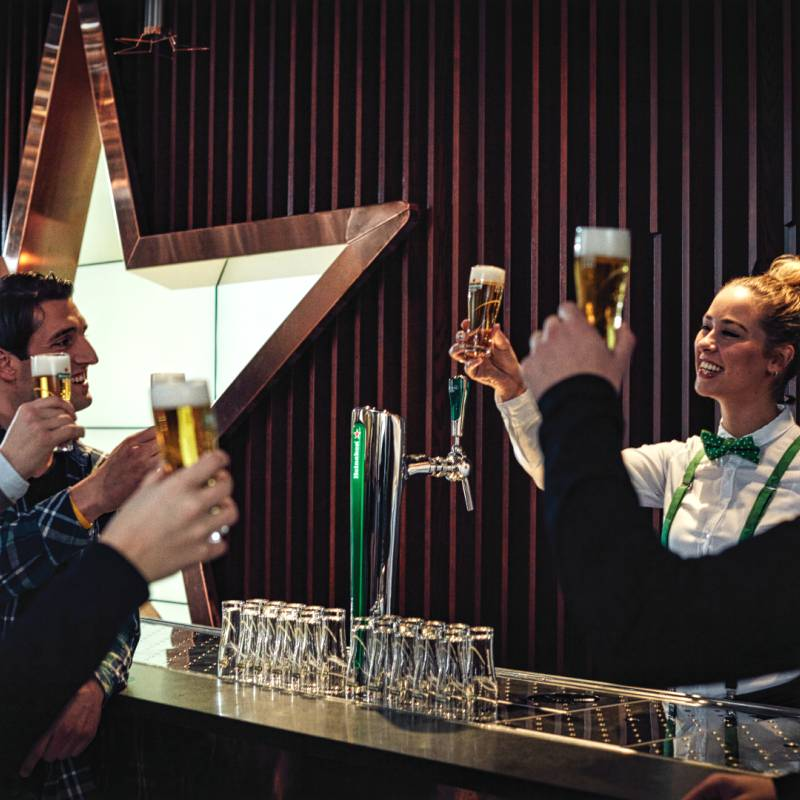 People toasting with a Heineken beer at the bar in the Heineken Experience.