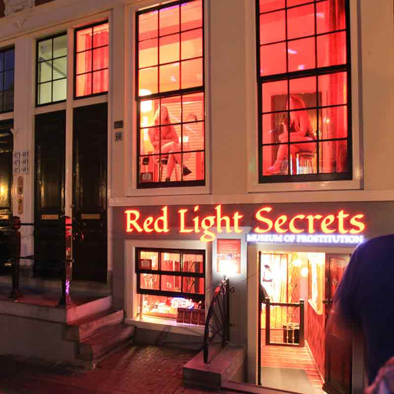 The entrance of the Red Light Secrets museum at night with two girls sitting behind the window
