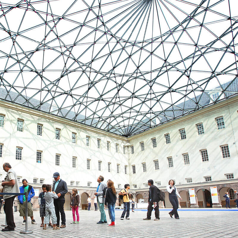 People standing in line at the hall of the Maritime museum with a glass roof with a pattern above them.