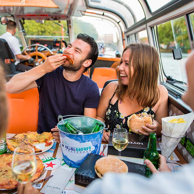 Two people laughing and eating burgers and pizza on the burger and pizza cruise.