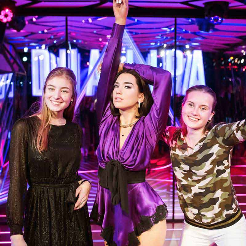 Two girls posing next to the statue of wax of Dua Lipa at Madame Tussauds