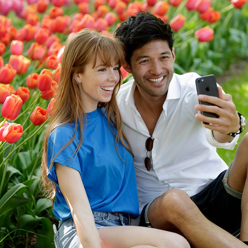 Couple taking a selfie with tulips in the back at the Keukenhof garden.