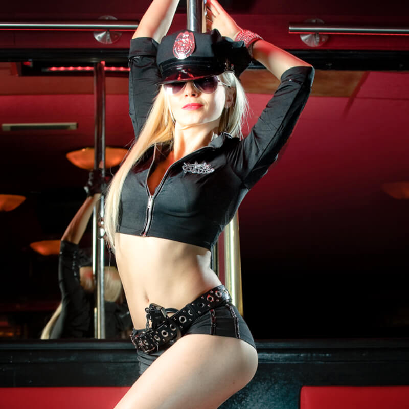 A dancer from Casa Rosso dancing on a pol with a sexy police outfit on.