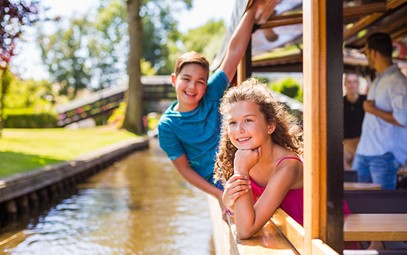 Two children in a boat on a canal in Giethoorn.
