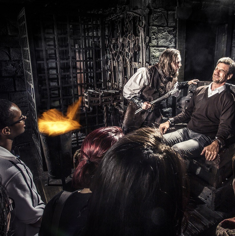 A visitor of the Amsterdam Dungeon sitting in a chair while an actor dressed in medieval clothing points a stake at him.