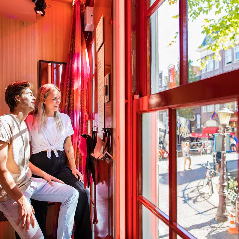 Two people looking out of a red light window at the prostitution museum Amsterdam.