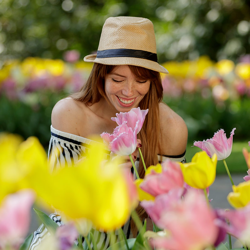 Woman with a hat smelling flowers at the Keukenhof flowergarden.