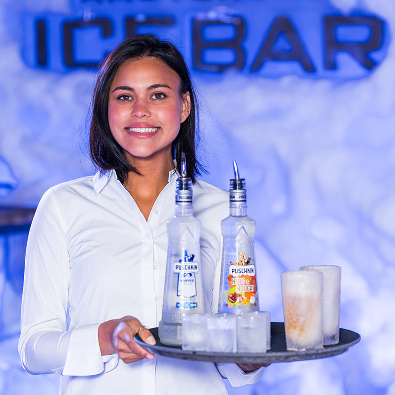 Server at the Amsterdam Ice Bar holding a tray with wodka bottles and glasses made from ice.