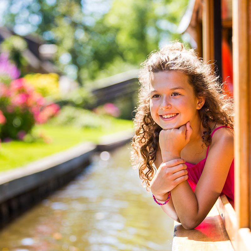 A girl hanging out the window of a boat midst a canal cruise during the Giethoorn tour.