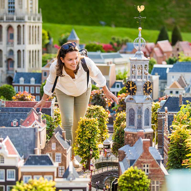 Woman walking between the miniature houses in Madurodam.