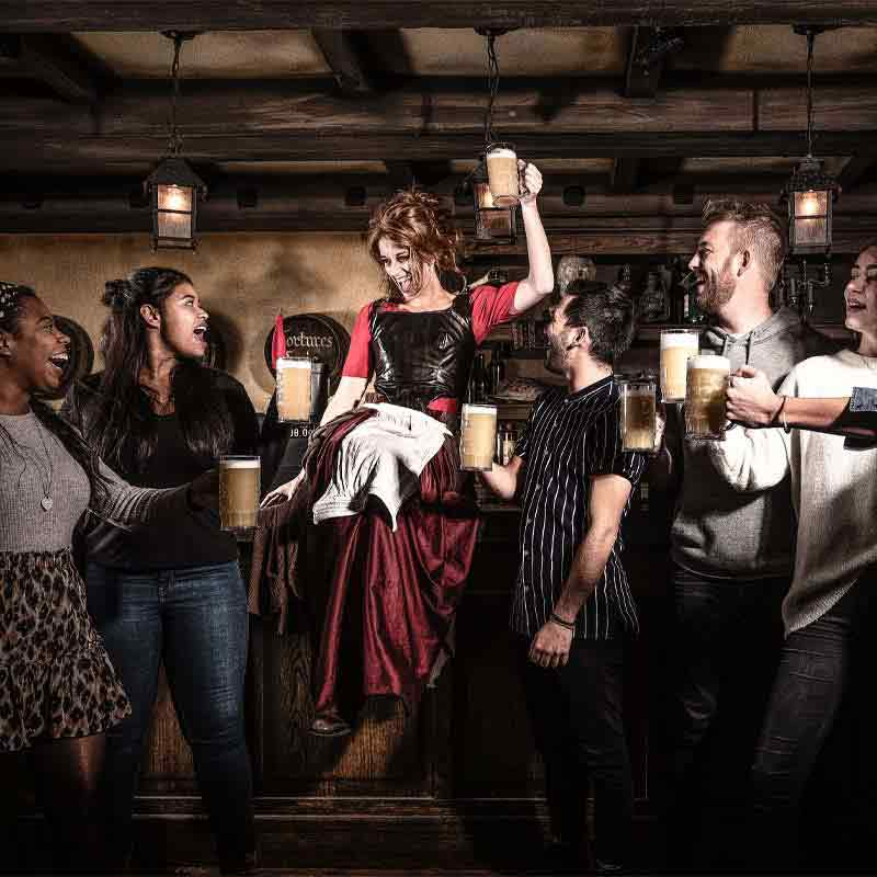 People smiling and drinking big beers with a woman in medieval clothing at the Amsterdam Dungeon