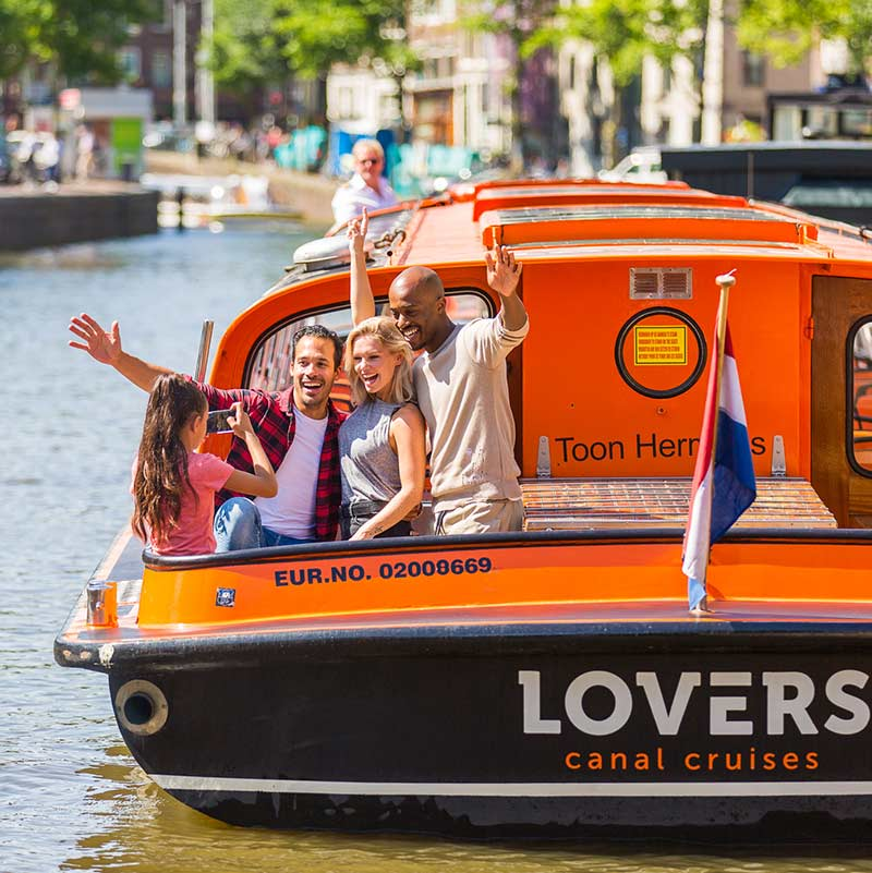 A girl taking a picture of people on the back of a Lovers Canal Cruises boat.