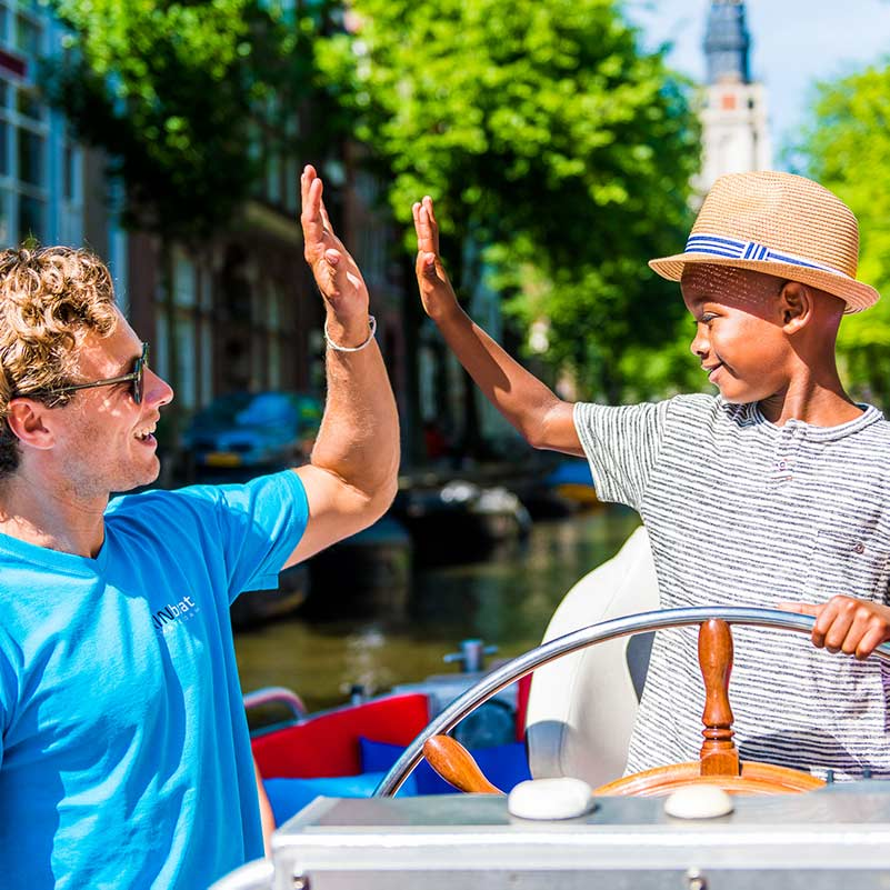 Boy with a hat takes the helm of the Cruise like a local boat and high fives the skipper.