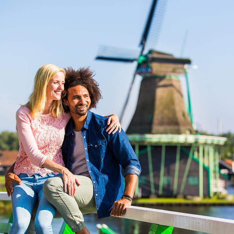 A man and a woman sitting on a wooden fence in front of a windmill in the Dutch Countryside.