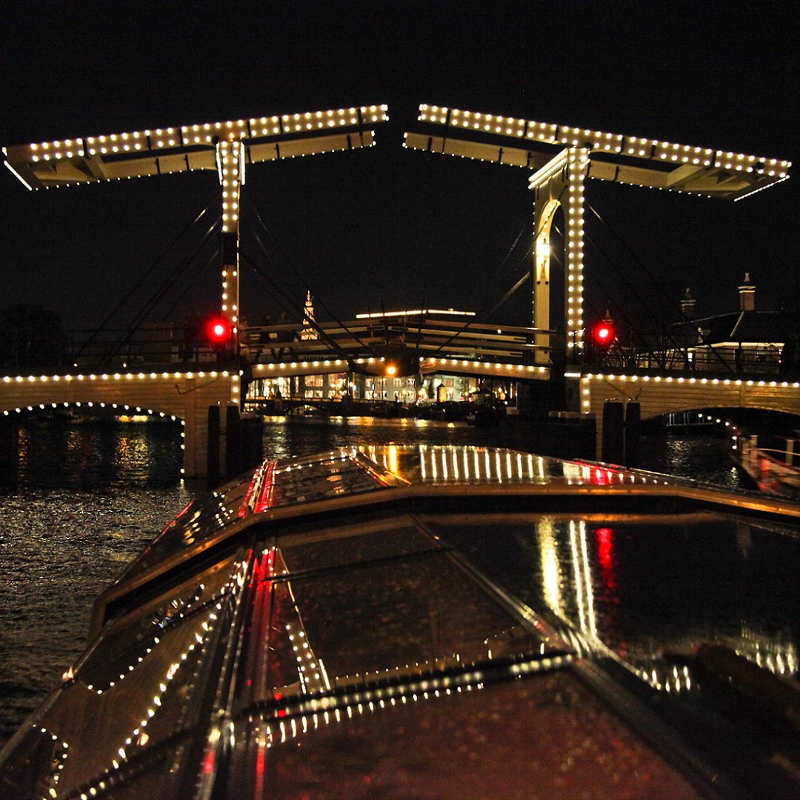 A bridge over an Amsterdam canal lit up in the dark, with a boat in the fore front.