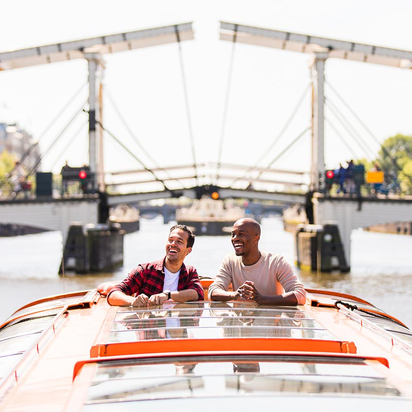 Two man sticking their heads out of a canal cruise boat with the Skinny Bridge in the background.