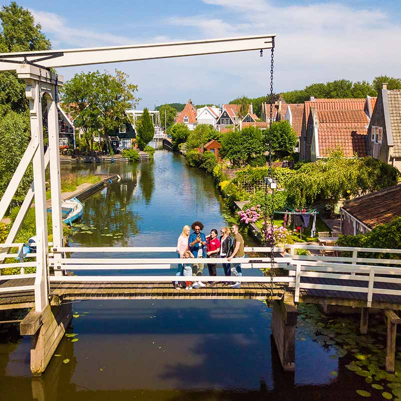 Group of people standing on a bridge in a traditional Dutch village.