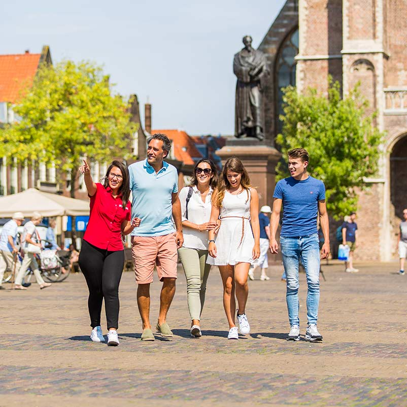 Four people and a guide walking in Delft during the Delft, The Hague & Madurodam tour.
