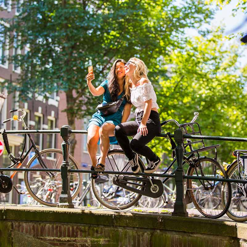 Two women sitting on a bridge in Amsterdam making a picture of the both together.