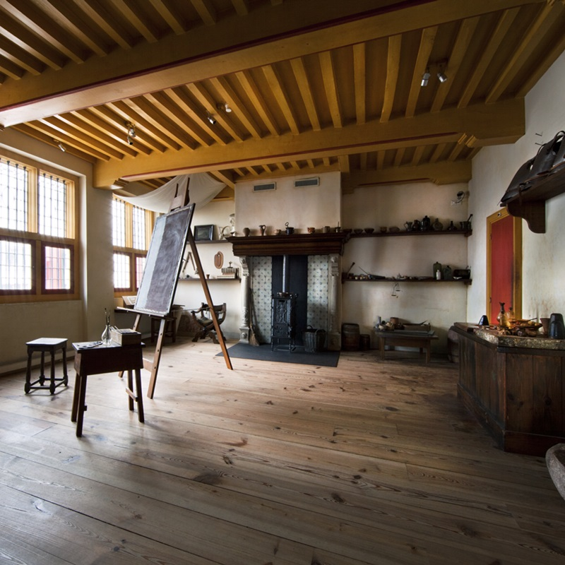 View of the inside of the Rembrandt house museum with an easel and painting products.
