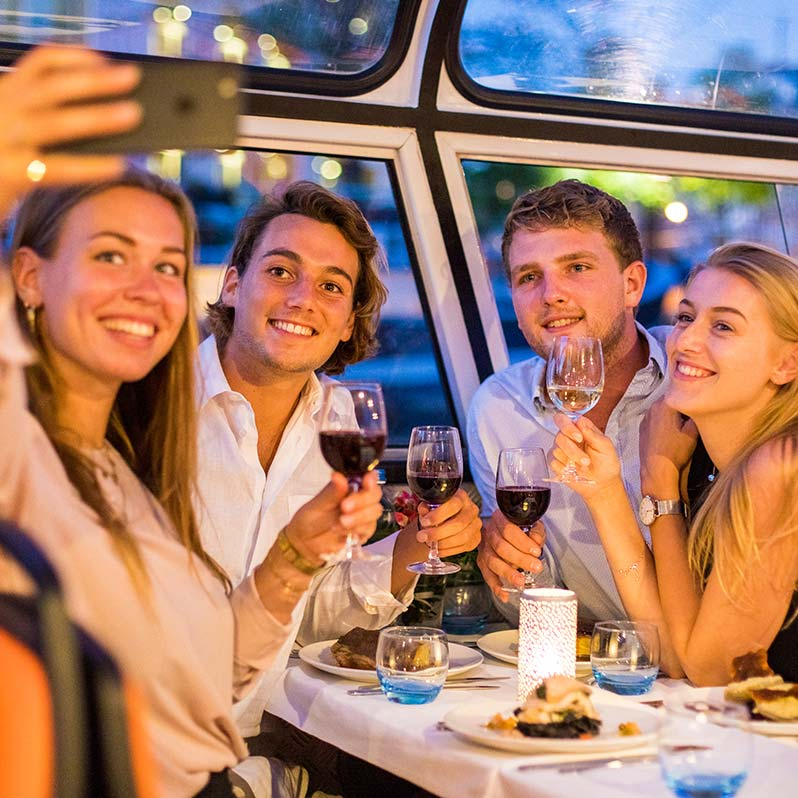 Four people taking a picture with glasses of wine on the Amsterdam dinner cruise.