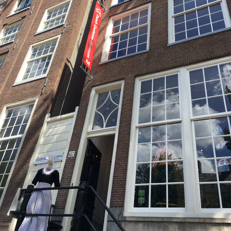 The front door of the Dutch costume museum with a doll in traditional Dutch clothing standing in front of it.
