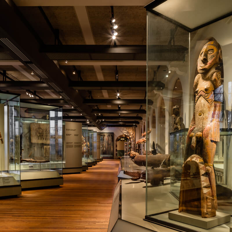 View of an exhibition in the Tropenmuseum Amsterdam, a wooden statue of a human in the forefront.