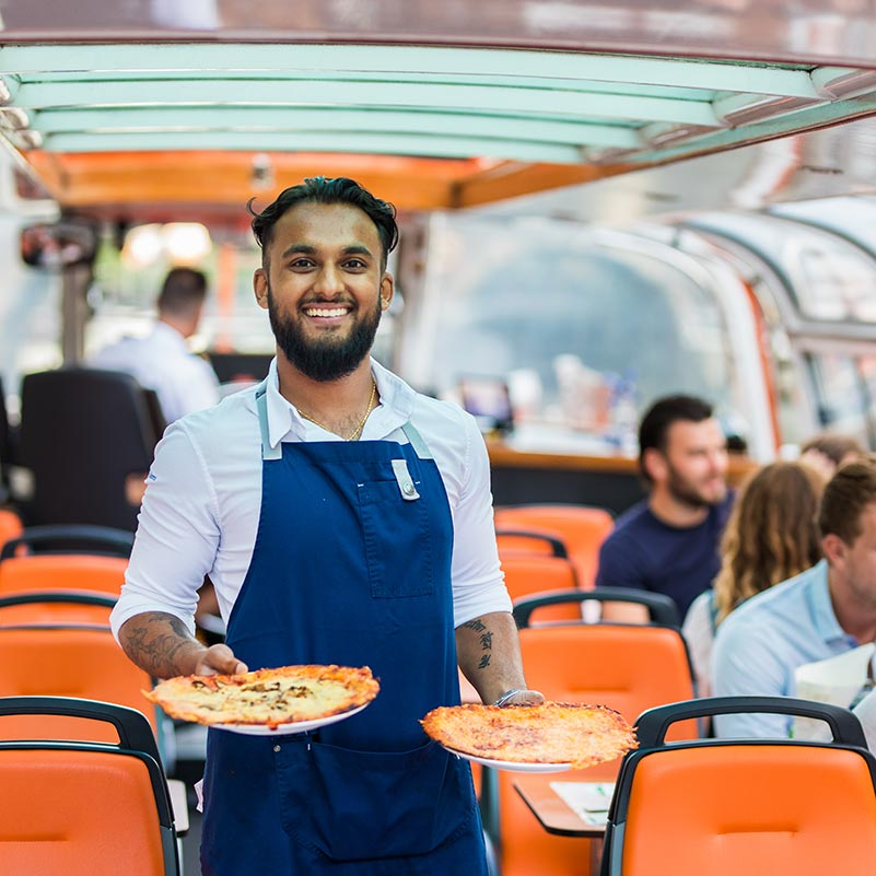 Server smiling with two pizza's in his hands at the Amsterdam Pizza cruise boat.