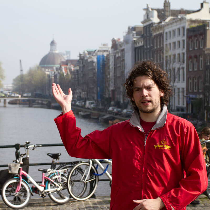 A guide of the Amsterdam City Bike Tour pointing at something behind him.