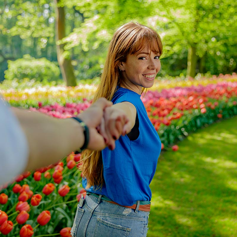 Woman holding hands with someone and looking in the camera with tulips in the back at Keukenhof.