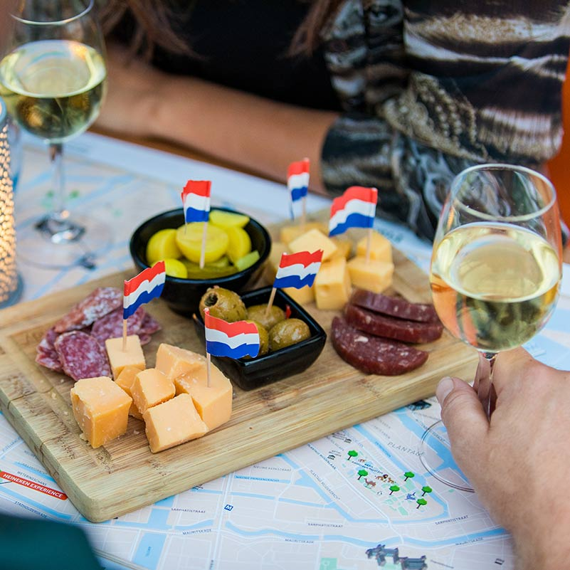 A plate of charcuterie and cheese and two wine glasses on the Romantic Cruise Amsterdam.