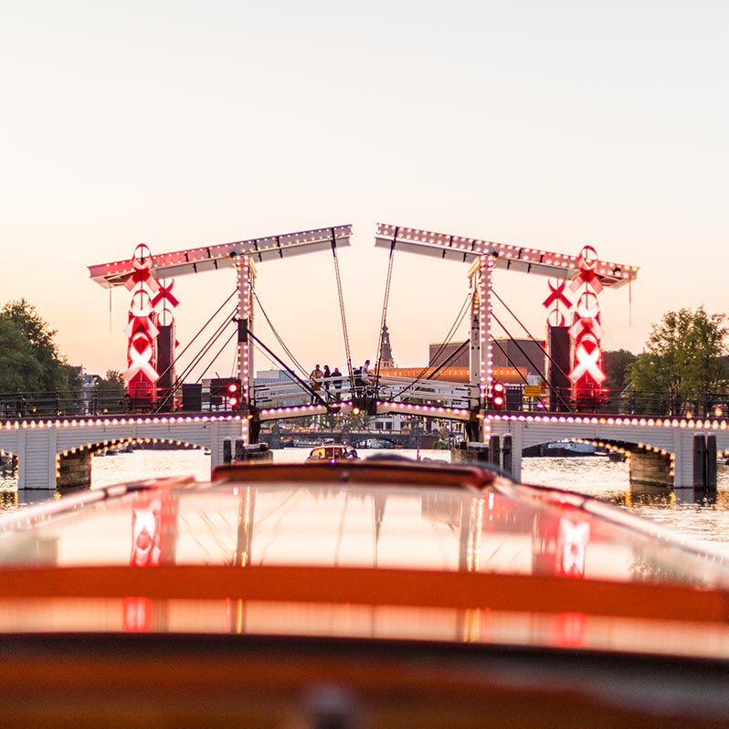 View of the Skinny Bridge in the evening from the top of the Amsterdam dinner cruise boat.