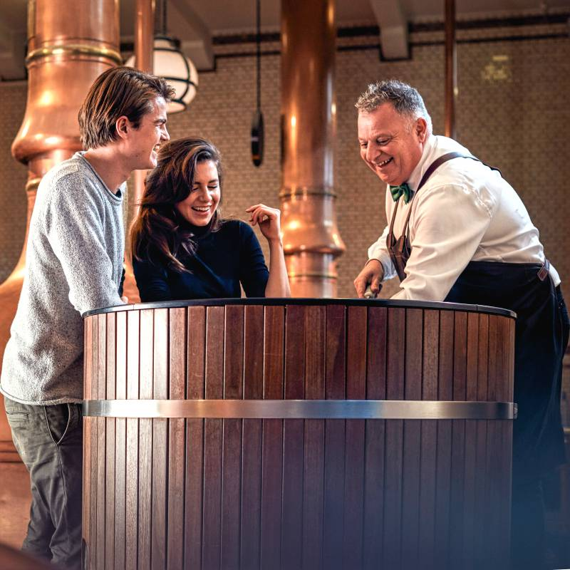 An employee at the Heineken Experience in Amsterdam shows two visitors how the beer is made.
