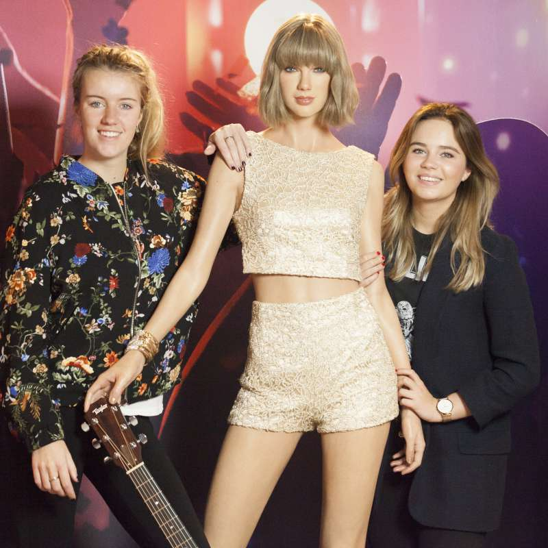 Two people standing next to a wax figure of Taylor Swift at Madame Tussauds Amsterdam.
