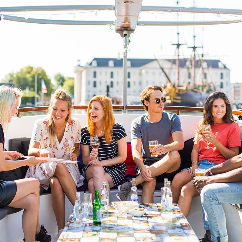 Six people sitting on the Dutch Authentic Boat chatting and drinking together.