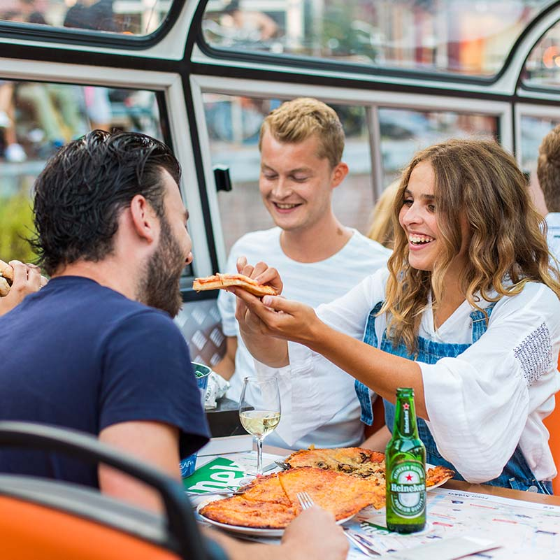 Three people sitting at a table during the Amsterdam Pizza Cruise, one is feeding pizza to the other.