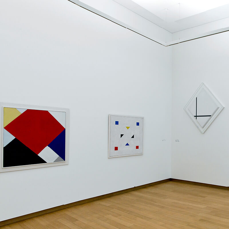 Three paintings in white, black, yellow, red and blue at the Stedelijk Museum in Amsterdam.