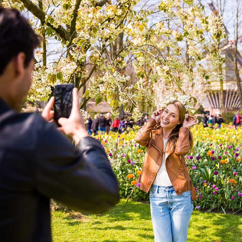 Man taking a picture of a woman in the Keukenhof with flowers in the back.