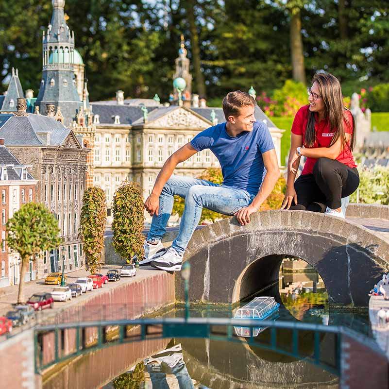 A man and a guide sitting on a miniature bridge in Madurodam during the Rotterdam, Delft & The Hague tour.