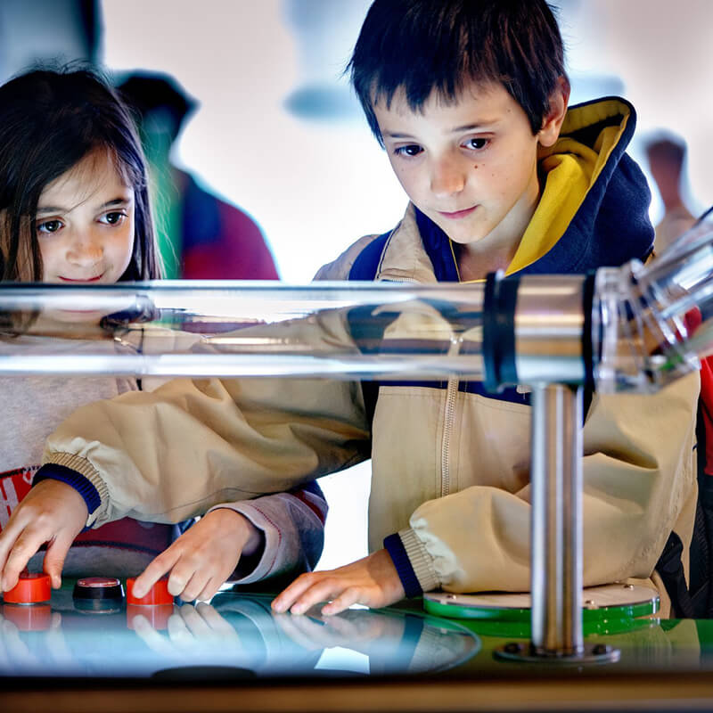 Two children using buttons to do a science experiment at Nemo Amsterdam.