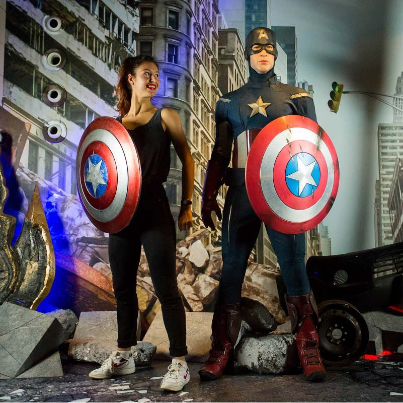 Woman holding a Captain American shield while standing next to a wax figure of Captain America at Madame Tussauds Amsterdam.
